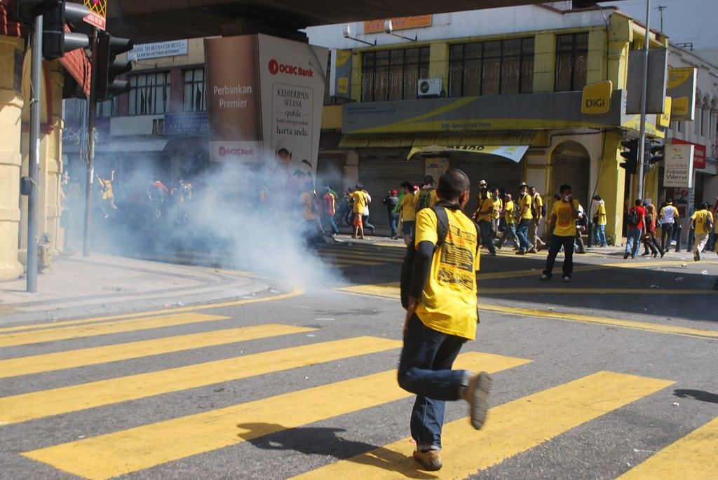 Protestors flee teargas near Masjid Jamek in Kuala Lumpur on Saturday (Photo: Simon Roughneen)