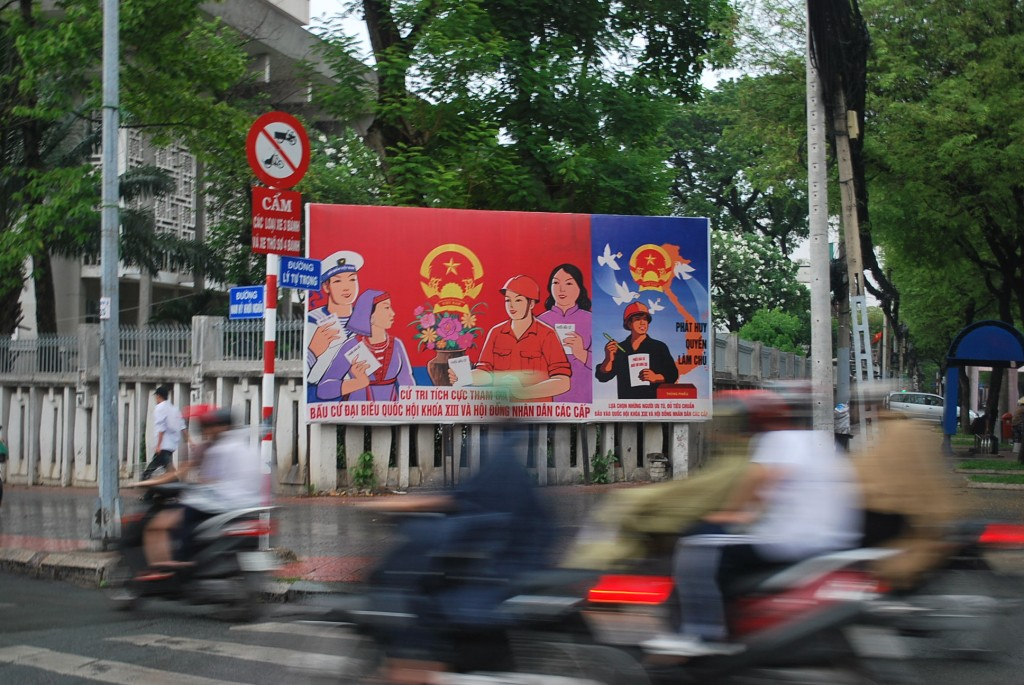 Motorcyclists in Ho Chi Minh City zip past a sign urging Vietnamese to vote in 2011 elections. Of the 500 seats available, 458 went to the Communist Party. (Photo: Simon Roughneen)