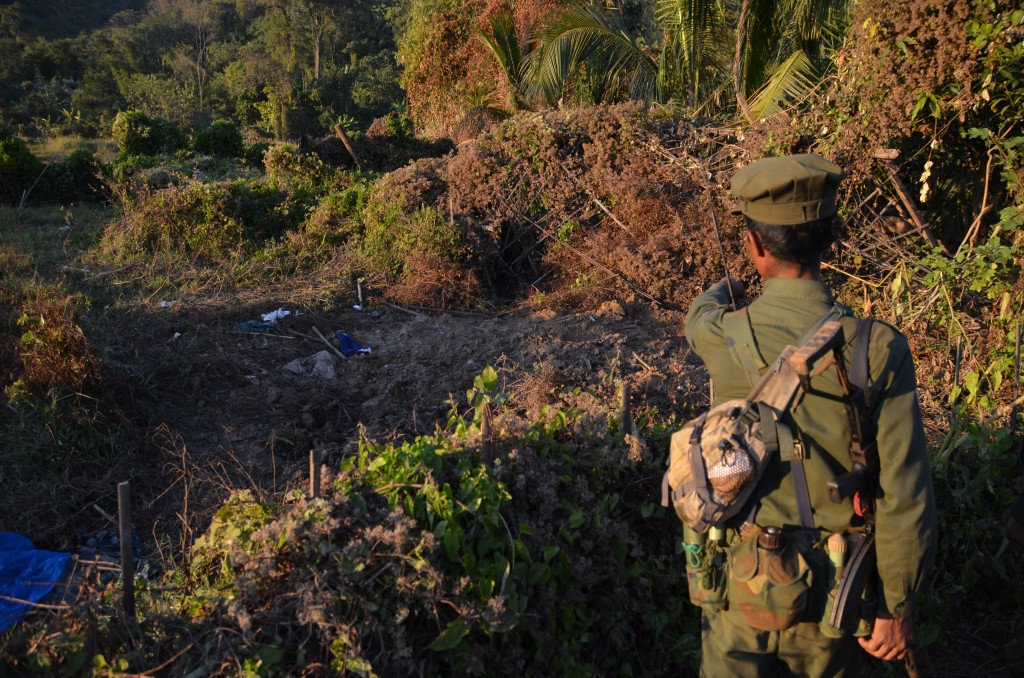 A soldier shows where the KIA says it buried 12 Burma Army soldiers who were killed on Dec. 14. (Photo: Simon Roughneen