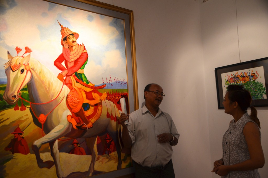 Burmese artist Myat Kyawt discusses his version of a famous old hagiography of Gen Maha Bandoola, who led the Burmese army against the invading British during the first Anglo-Burmese War. (Photo: Simon Roughneen / The Irrawaddy)