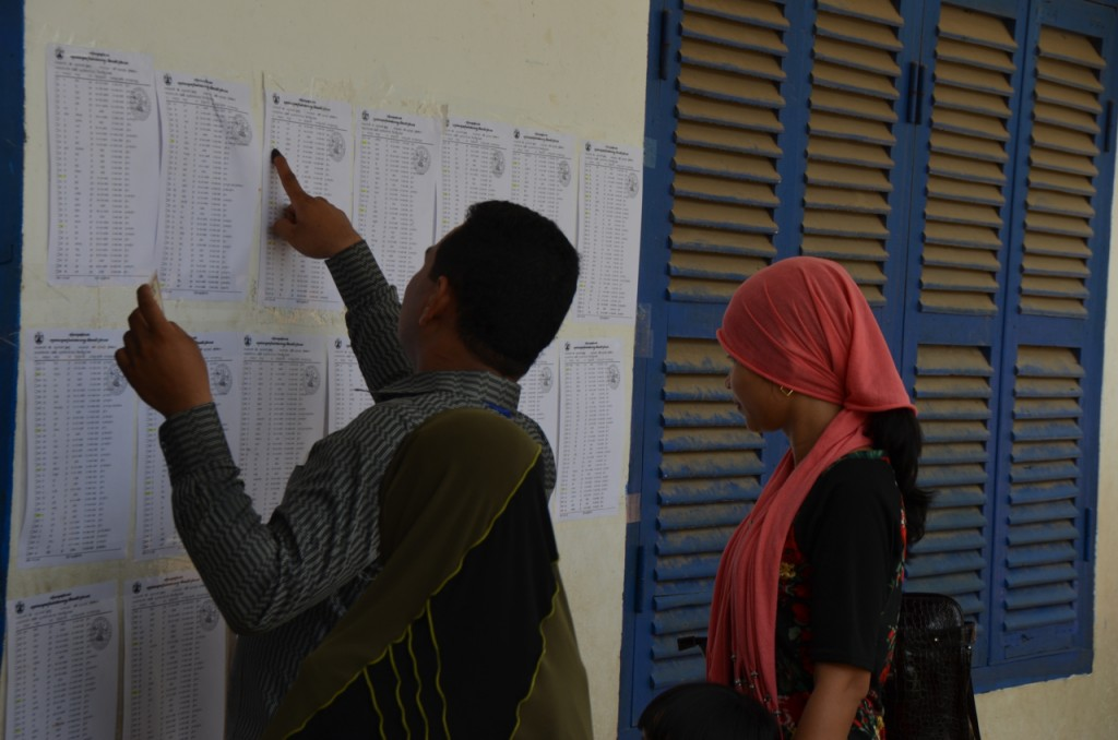 Voters chcking for their names on polling station list at an Islamic school polling station on Phnom Penh's outskirts (Photo: Simon Roughneen)