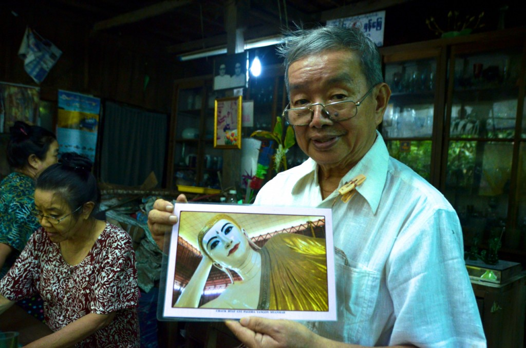 Myat Kywe holds a photo of the Chauk Htat Gyi reclining Buddha (Photo: Simon Roughneen)