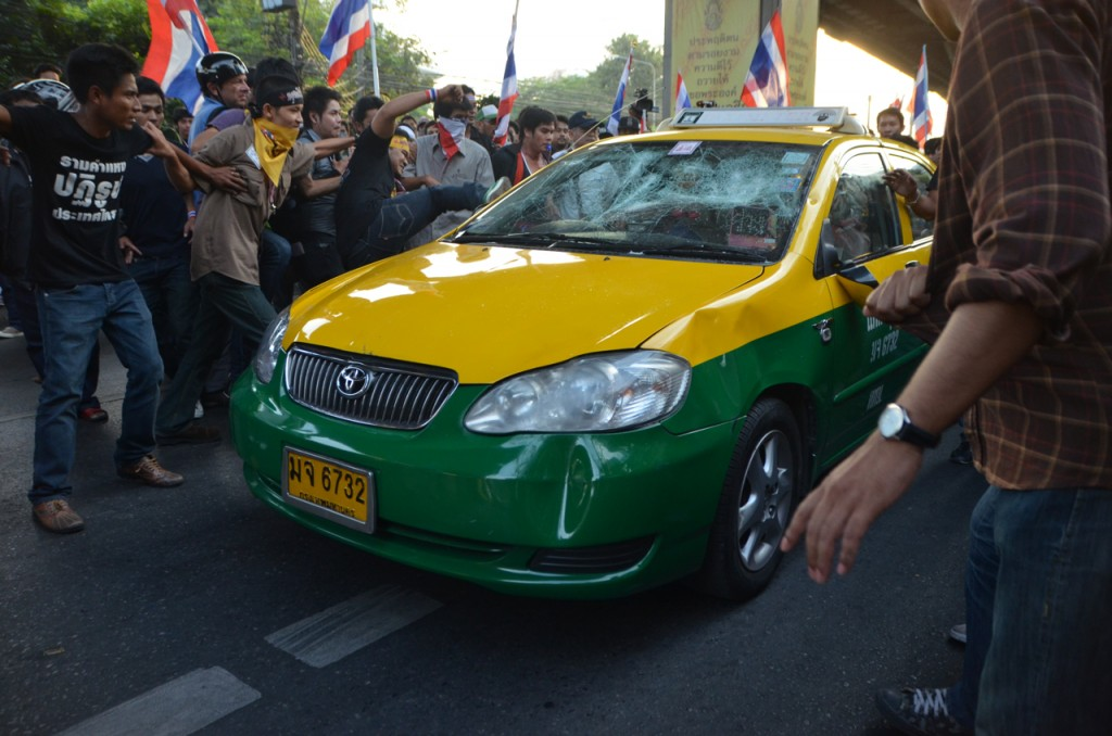 Anti-government protestors in Bangkok attack taxi perceived as pro-government on Saturday (Photo: Simon Roughneen)