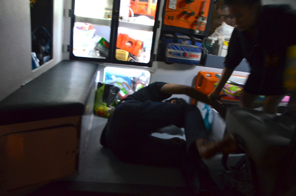 Injured student protestor loaded into ambulance inside Ramkhamhaeng University after clashes (Photo: Simon Roughneen)
