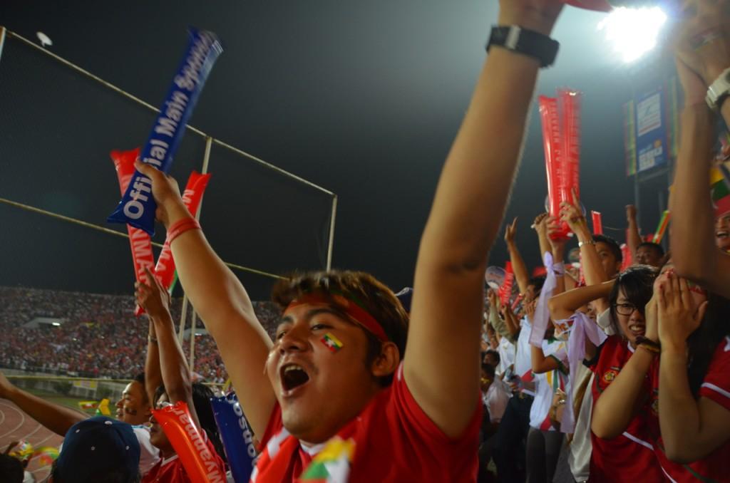 Burmese fans cheer as their sides' goal goes in againsy Thailand at the SEA Games football tournament (Photo: Simon Roughneen, Dec. 15 2013)