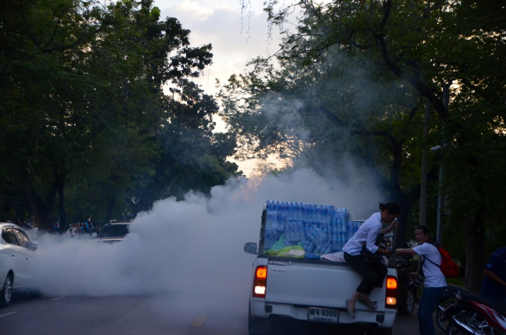Protestors flee supply truck as tear gas lands (Photo: Simon Roughneen)