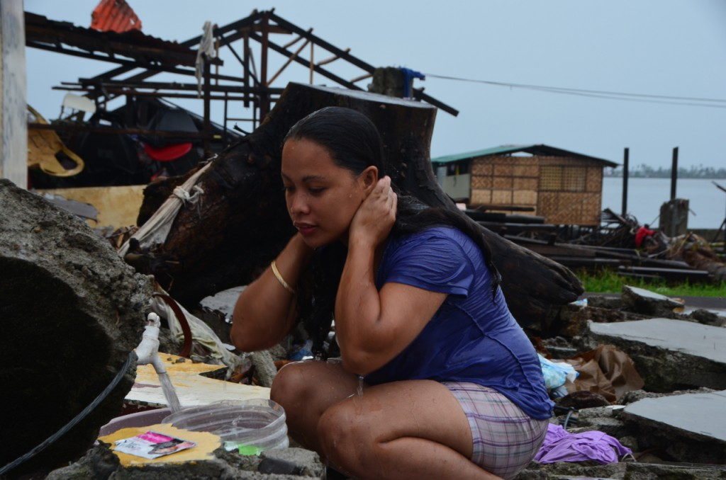On Christmas Day, woman washes using broken waterpipe running along Tacloban's destroyed waterfront (Photo: Simon Roughneen)