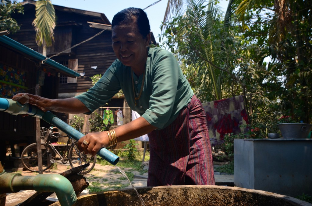Woman works water pump in northern Rangoon (Photo: Simon Roughneen)