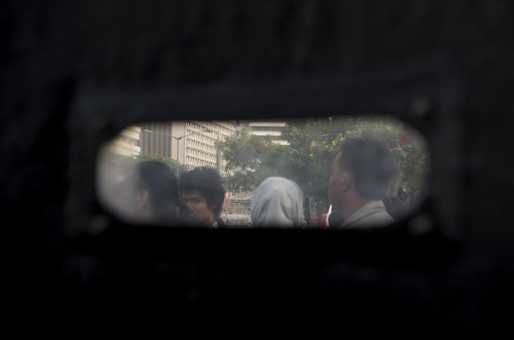 View through police shield after tear gas fired at Prabowo Subianto supporters on Aug 21 (Photo: Simon Roughneen)